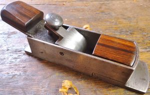 "George Thorested small cast iron mitre plane, circa 1854-1858, 6 3/8"" long, with 1 1/2"" iron. Its 5/8"" shorter than a Stanley No. 19 block plane, but Thorested's was discontinued a good 30 years before the No. 19 was introduced in 1888. Besides, the solid feel and accuracy of the Thorested mitre bears little comparison to the Stanley, save that they both have bevel down irons and adjustable mouths. This mitre has excellent fit and finish, and attention to detail, noting the heavily chamfered lever cap, and tight mouth. On the side, you can see the screw-through lever cap cross pin, and if you look closely at the top of the side, there are a couple pin head size casting voids that were filled with copper brazing material by Thorested."