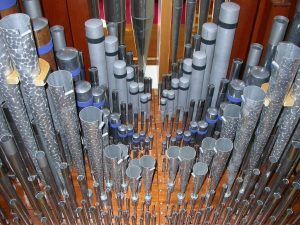 View of the Great windchest, showing pipes made variously of lead, tin, copper and spotted metal. This is the organ's primary division and stands at the top of the case immediately behind its facade of polished tin 8′ Principal pipes. From http://upcch.org/music/sanctuary-organ/